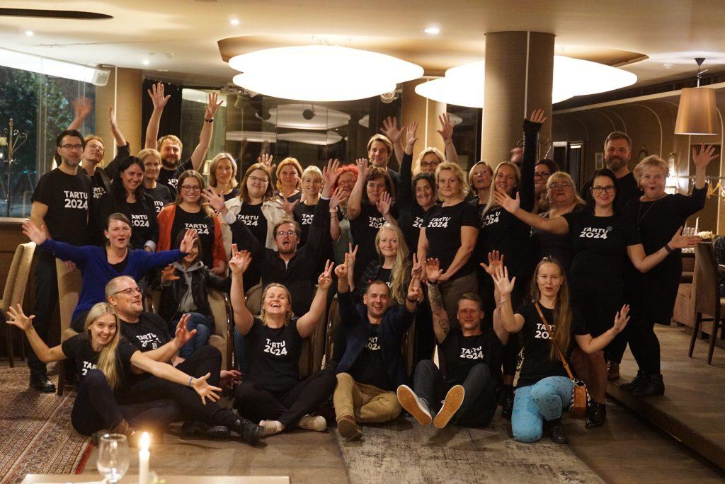 Kaunase delegatsiooni liikmed rõõmsate nägudega  lehvitamas